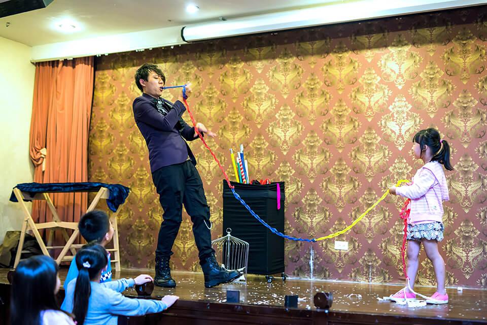 原來是我們魔術師小煜,在眾目睽睽之下從嘴巴裡面拉出了一條彩色的絲帶